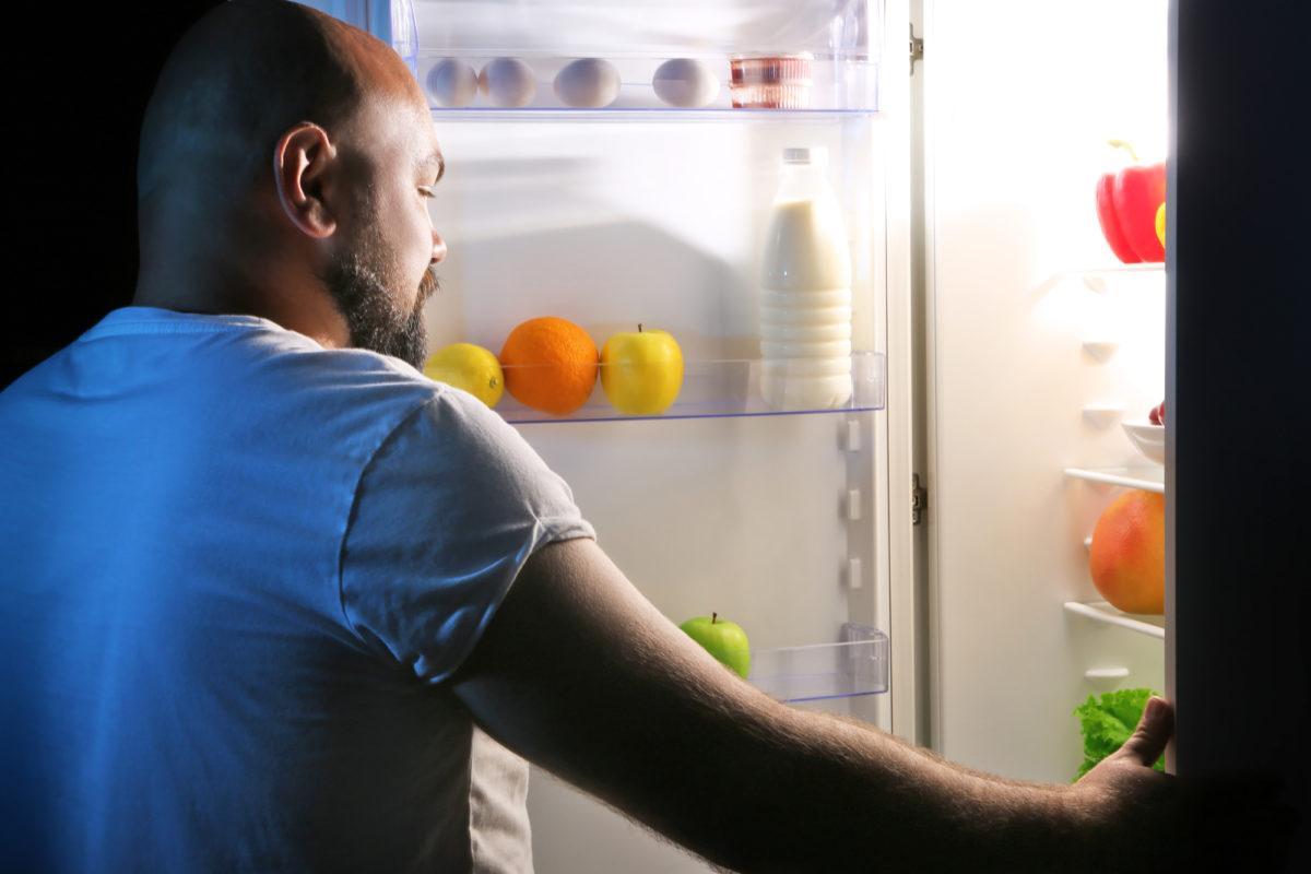 Man taking food from his new refrigerator.