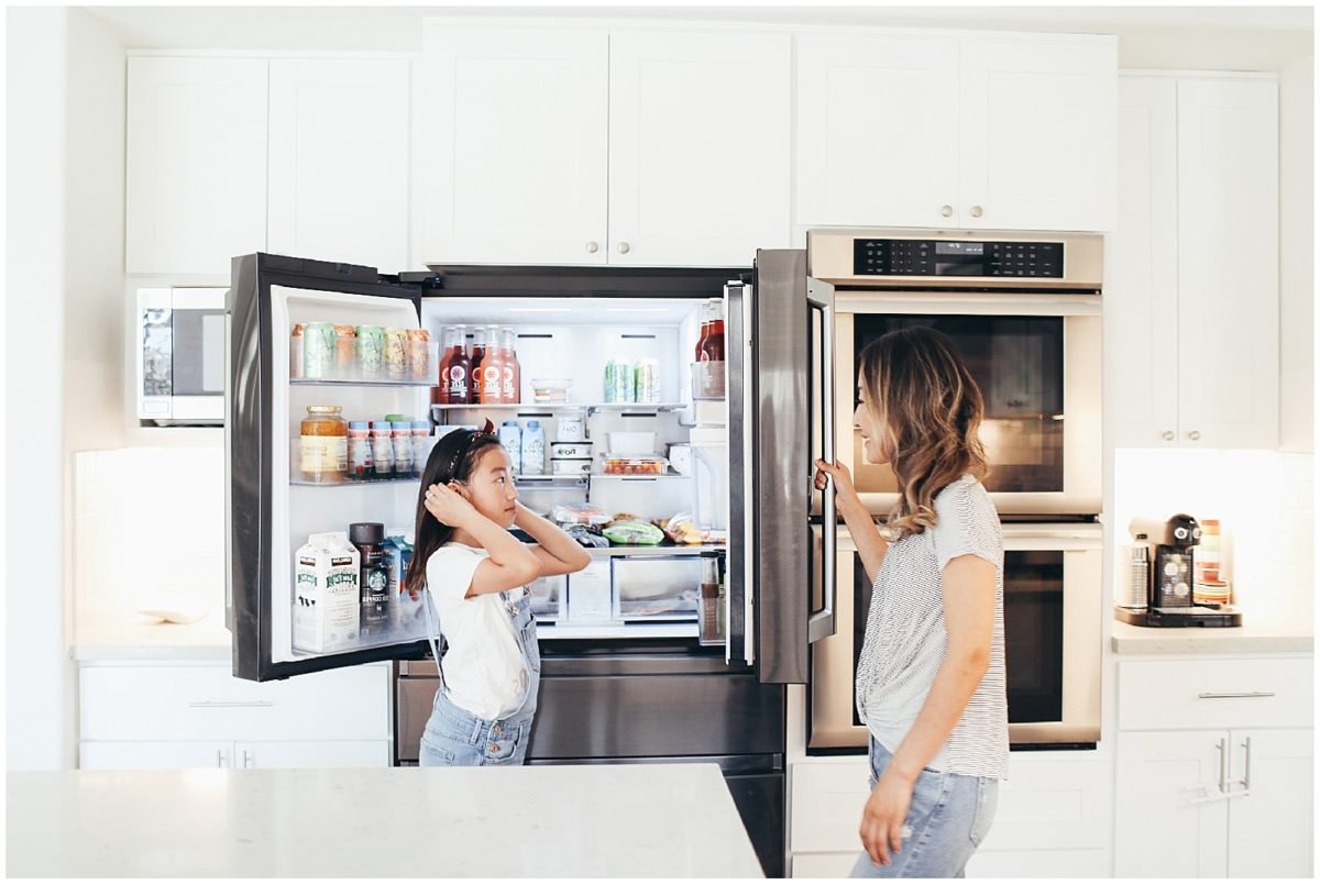 Gloria and her daughter talking in the kitchen while they close the french door refrigerator.