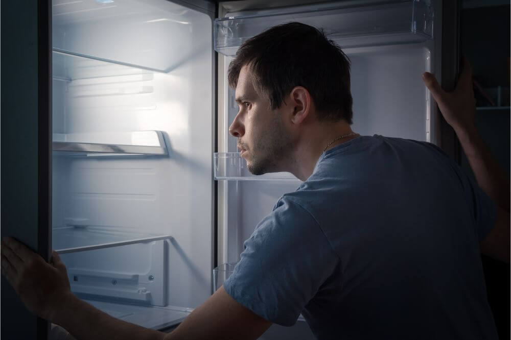 man looking inside of the refrigerator