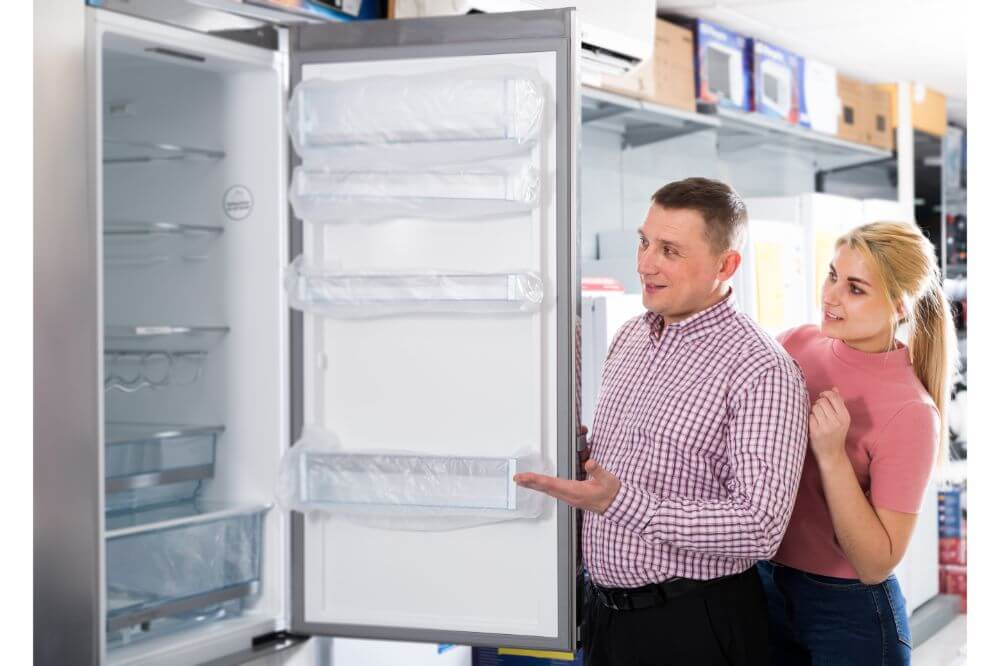 couple looking at new refrigerator