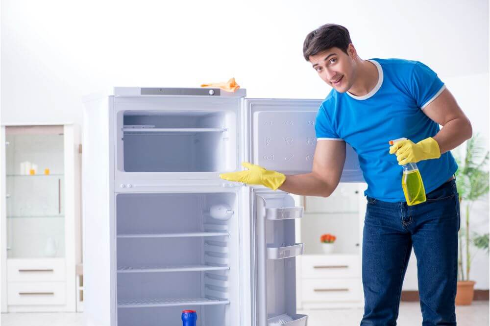Man with gloves and spray cleaning fridge