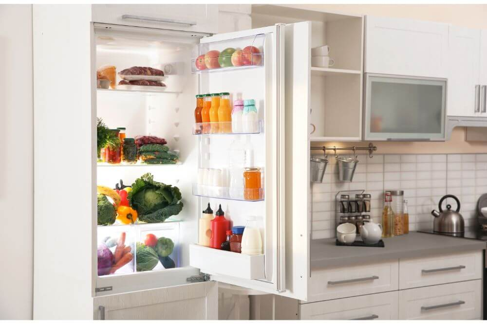 White double door fridge with fruits, vegetables, and drinks