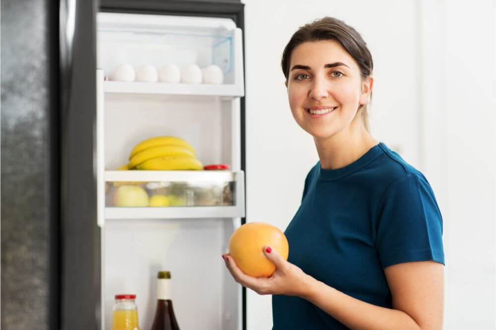woman holding a fruit beside refrigerator