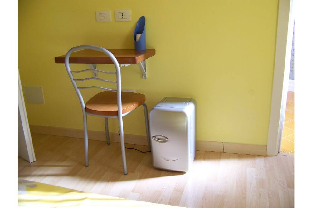 Mini fridge beside table and chair